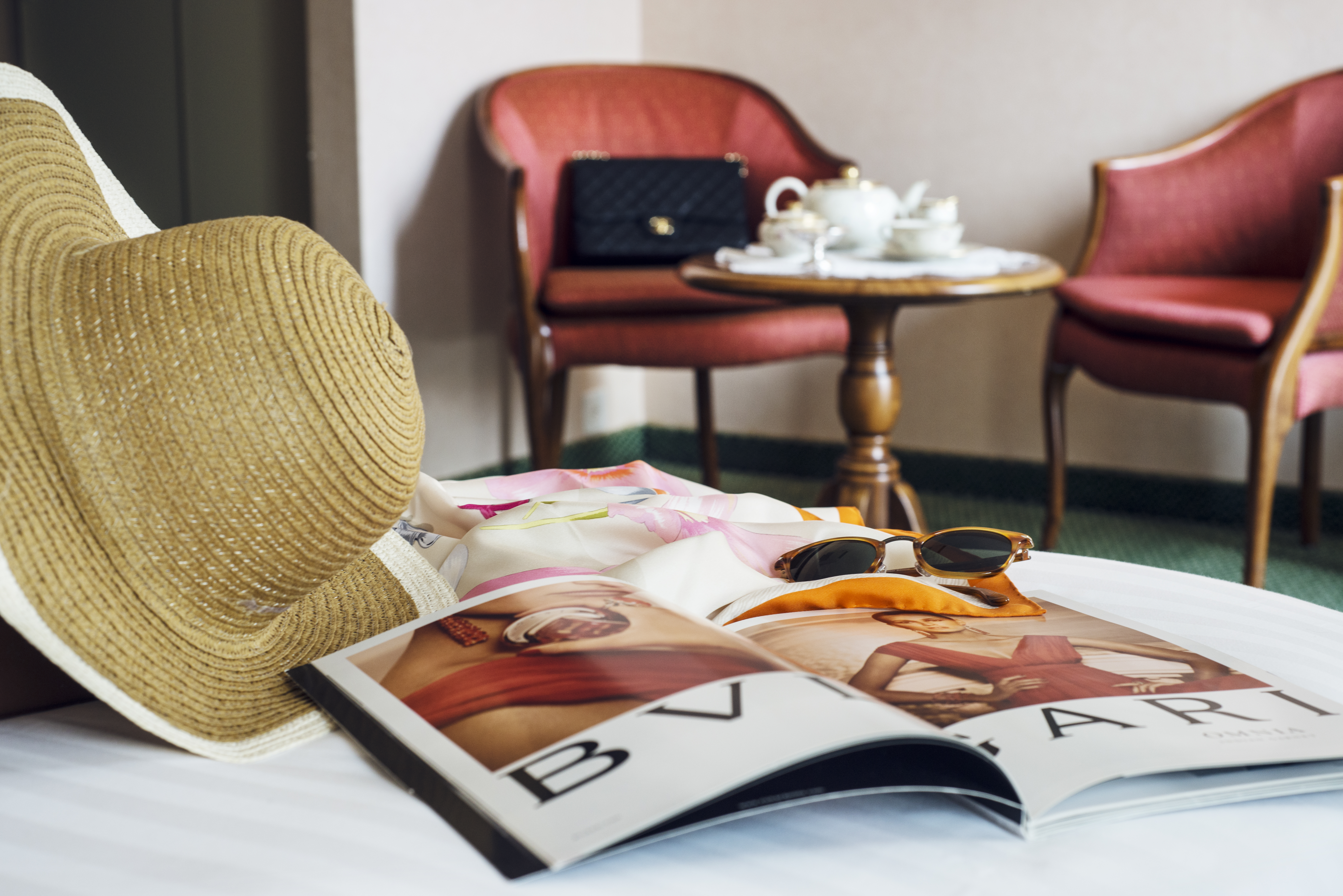 Magazine, sunglasses and hat lie on a white table
