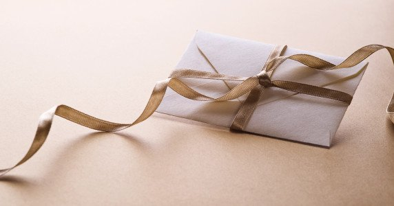 A white envelop decorated with a golden ribbon