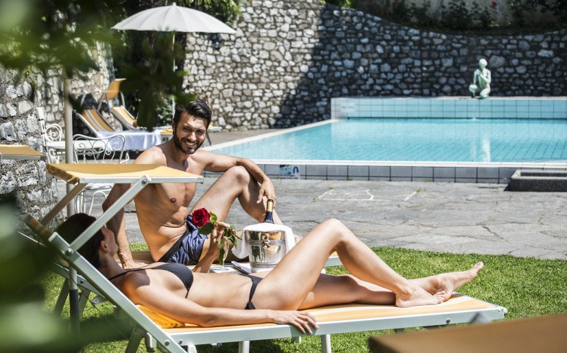 Two people sit on loungers near the pool