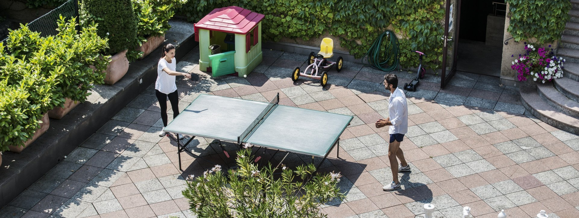 A couple is playing ping pong in the hotels garden