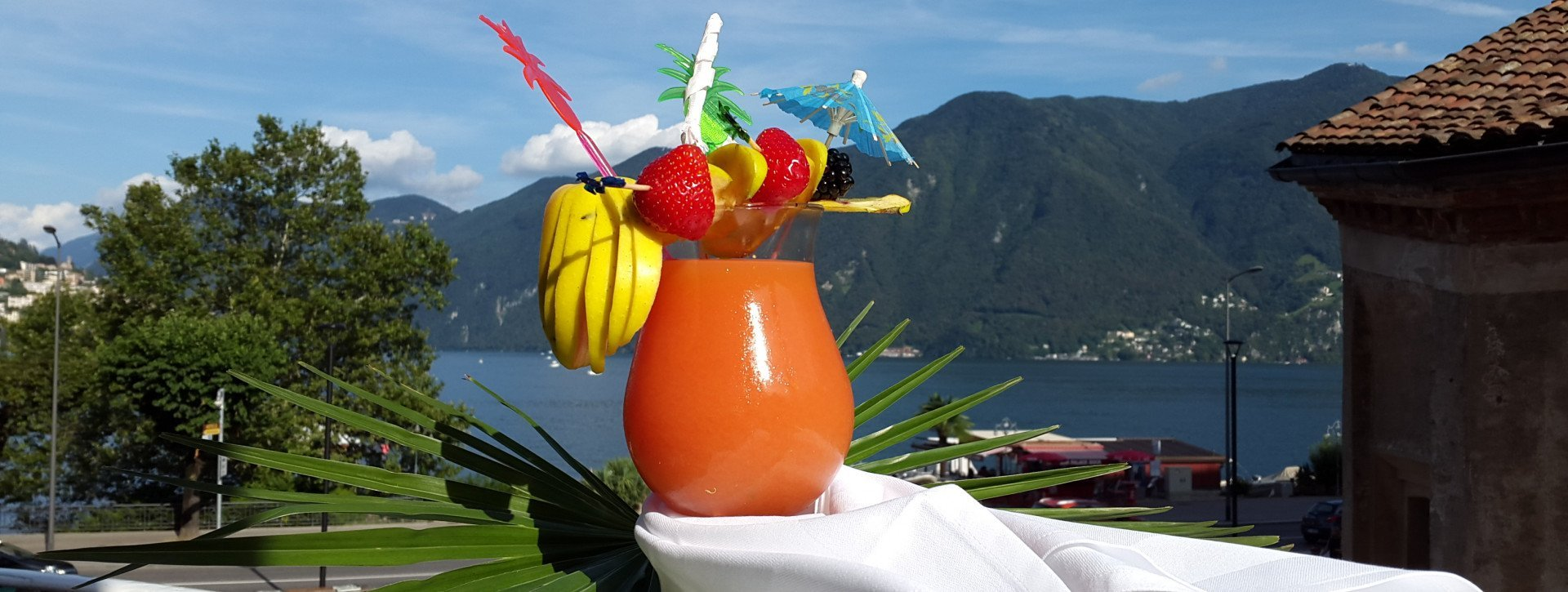An orange cocktail in front of the Lugano lake