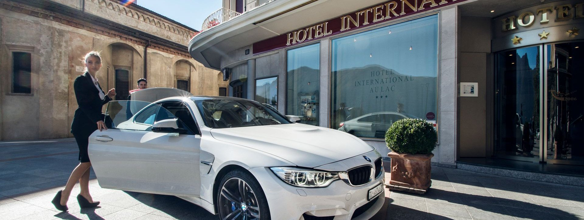 A couple arrive in a white BMW at International au Lac Historic Lakeside Hotel