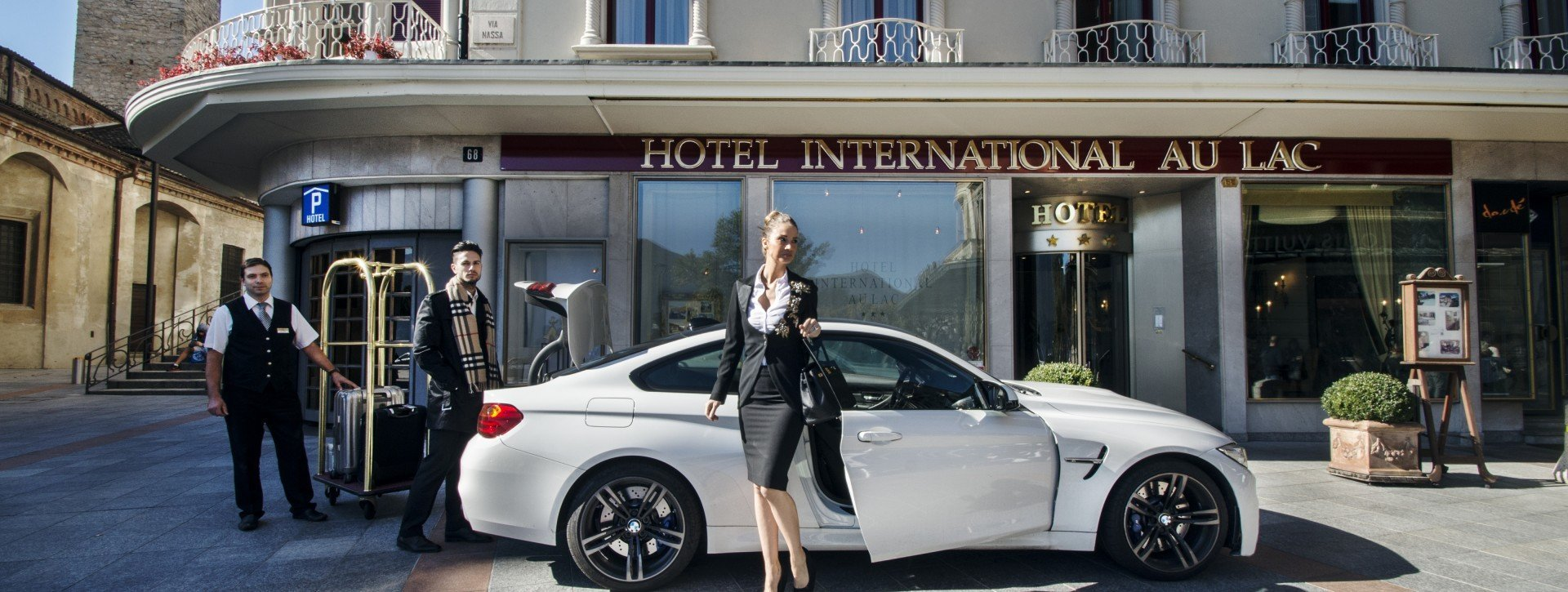 White BMW parks in front of the International au Lac Historic Lakeside Hotel