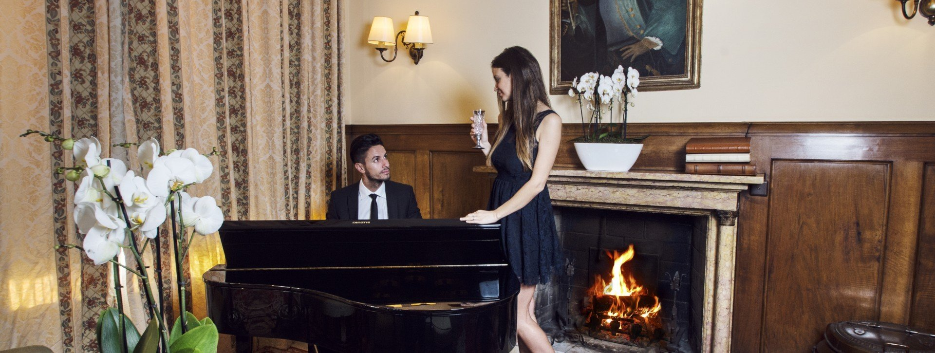 A man plays piano in the lobby bar and the woman stands beside him