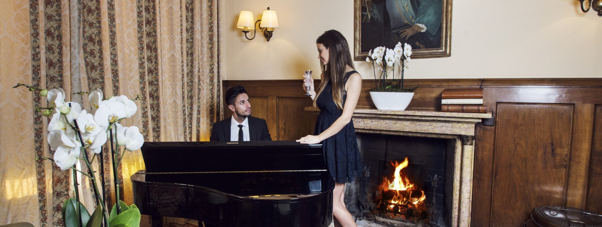 A young man plays piano while the woman is listening to him