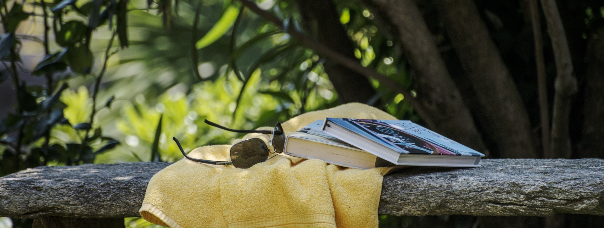 A towel, books and sun glasses