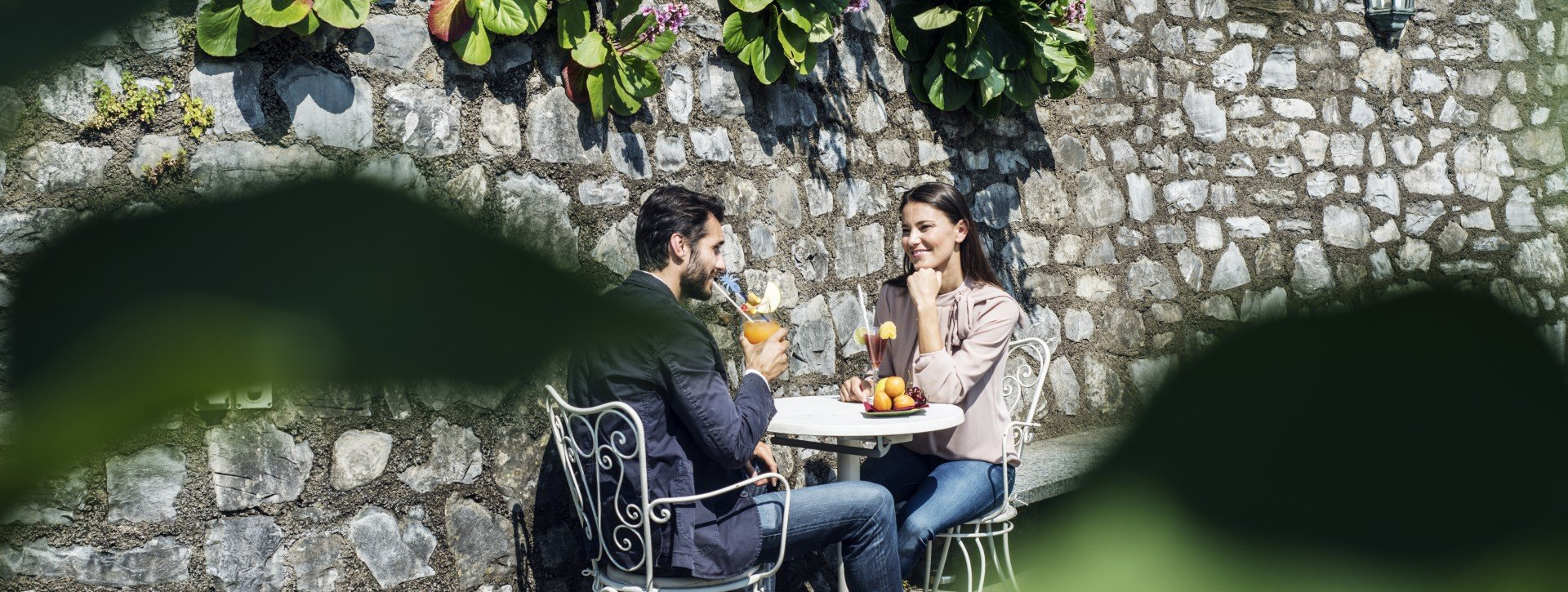 A couple have a drink in the garden of the International au Lac Historic Lakeside Hotel