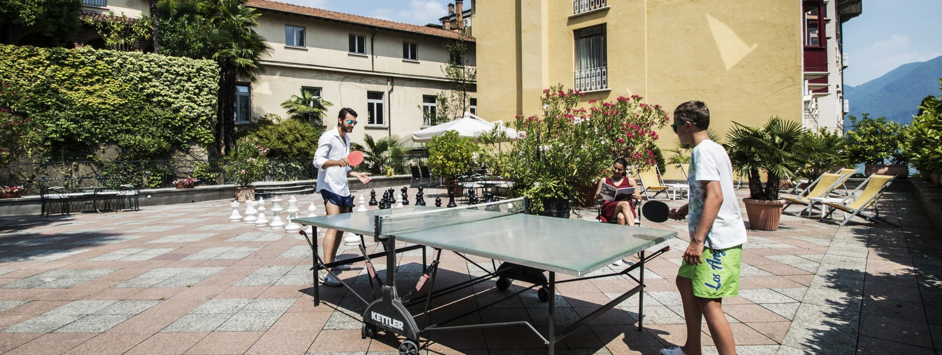 Two boys play ping pong in the sun