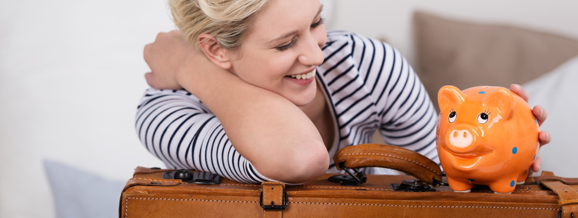 A blond woman is smiling at an orange piggy bank